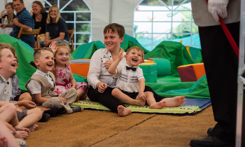 Children happily watching an entertainer during a christening