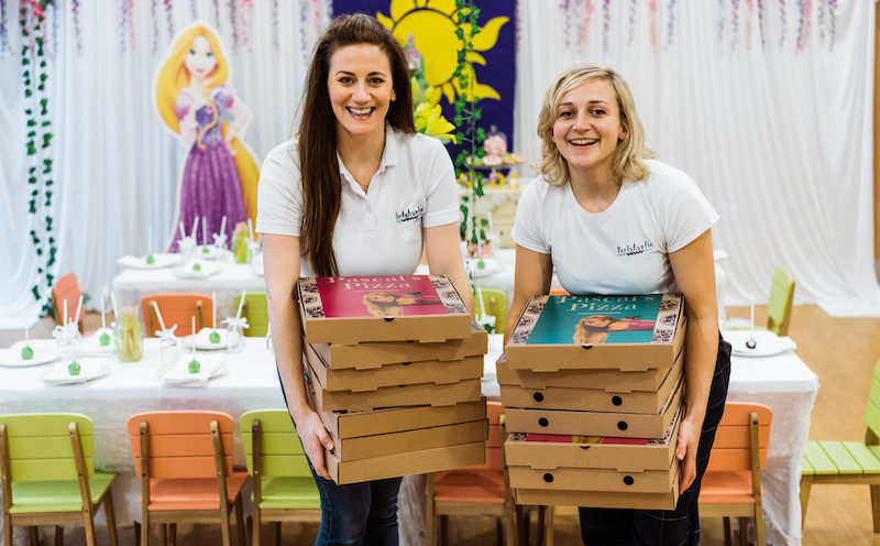 Two members of the Party Auntie staff smile whilst carrying pizza boxes